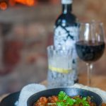 Image of dinner food and wine inside the Belle Balance Bush Hideaway home page of the website